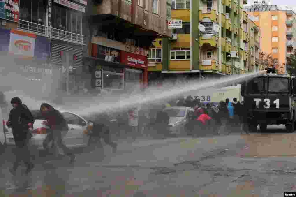 Turkish riot police use a water cannon to disperse Kurdish demonstrators during a protest in the southeastern city of Diyarbakir, against a curfew in Sur district and security operations in the region.