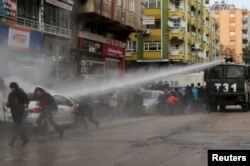 FILE - Turkish riot police use a water cannon to disperse Kurdish demonstrators during a protest against a curfew in Sur district and security operations in the region, in the southeastern city of Diyarbakir, Turkey, Jan. 17, 2016.