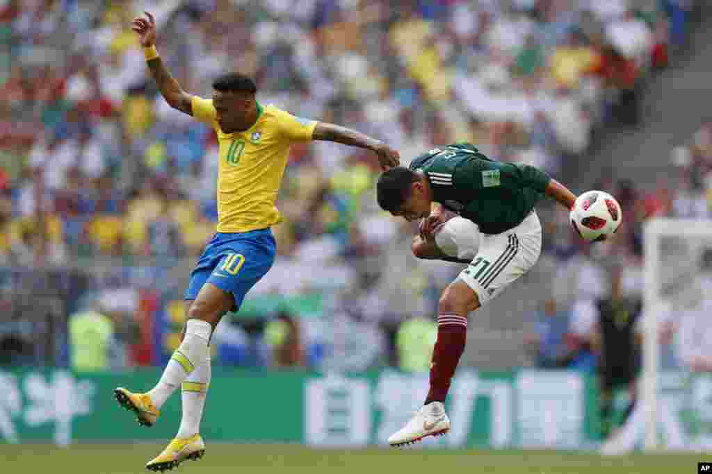 Brazil's Neymar, left, and Mexico's Edson Alvarez go for a header during their round of 16 match at the 2018 soccer World Cup in the Samara Arena, in Samara, Russia, July 2, 2018.