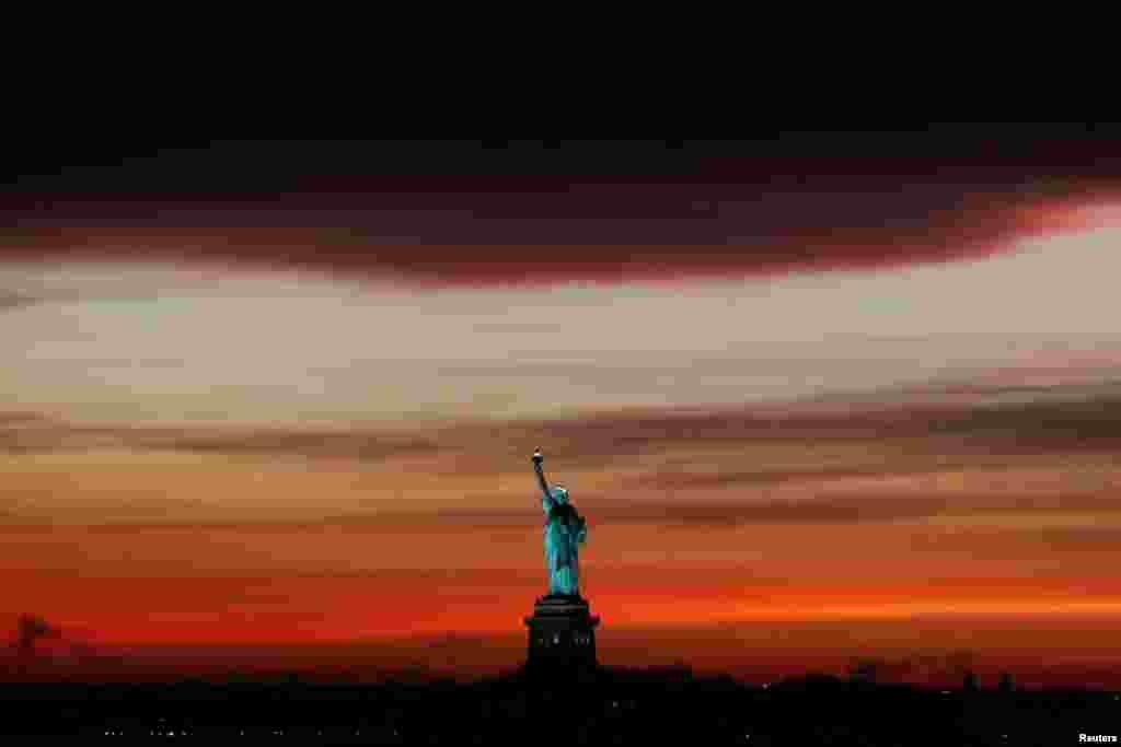 تصویری از مجسمه آزادی نیویورک به هنگام غروب آفتاب