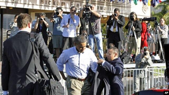 U.S. President Barack Obama dons his jacket before boarding Air Force One at Hickam Air Force Base in Honolulu November 15, 2011