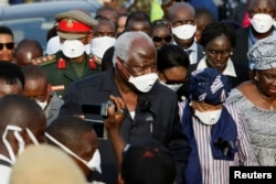 Sierra Leone President Ernest Koroma and Liberian President Ellen Johnson Sirleaf are seen on arrival for the burial of victims of the mudslide, at the Paloko cemetery, in Waterloo, Sierra Leone, Aug. 17, 2017.