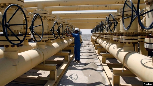 A worker adjusts a pipe at the Nassiriya oilfield in Nassiriya, southeast of Baghdad, Iraq, Sep. 8, 2012.