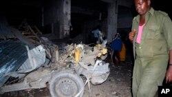 Un policier marche près du lieu d'une explosion d'un véhicuke piégé à Mogadiscio, Somalie.