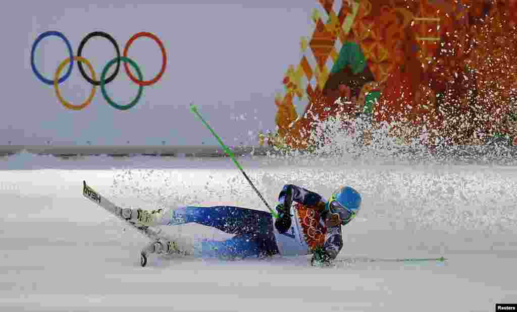 Winner Ted Ligety of the U.S. falls to the ground after the second run of the men's alpine skiing giant slalom event, Rosa Khutor Alpine Center, Feb. 19, 2014.