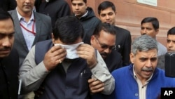 An unidentified member of India's parliament covers his face with a handkerchief after being affected by pepper spray gas in New Delhi, India, Feb. 13, 2014.