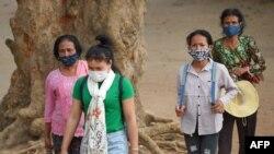Para pengunjung kuil Angkor Wat di Siem Riep, Kamboja, menggunakan masker di tengah kekhawatiran merebaknya virus corona COVID-19, Jumat, 6 Maret 2020. (Foto: AFP)