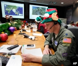 FILE - Air Force Lt. Col. David Hanson, of Chicago, takes a phone call from a child in Florida at the Santa Tracking Operations Center at Peterson Air Force Base near Colorado Springs, Colo., Dec. 24, 2014.