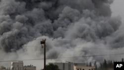 Asap tebal terlihat setelah serangan udara yang dipimpin AS di Kobani, Suriah, seperti terlihat dari pinggiran Suruc, di perbatasan Suriah dan Turki, Minggu (12/10).