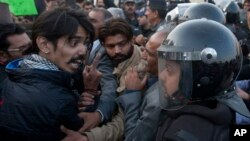 A civil society activist argues with police officers during a rally demanding recovery of the missing persons in Karachi, Pakistan, Thursday, Jan. 19, 2017. Pakistani police say a clash has been averted between the supporters of missing human rights activ