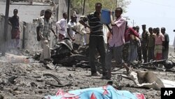 Residents gather near the covered remains of a suicide bomber at the scene of an attack along a street in Somalia's capital Mogadishu. A truck bomb killed at least 65 people at government buildings in the heart of Somalia's capital on Tuesday, an ambulanc