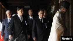 Japan's Land, Infrastructure, Transport and Tourism Minister Yuichiro Hata (2nd L) and other lawmakers are led by a Shinto priest after offering prayers to war dead at Yasukuni Shrine in Tokyo, August 15, 2012.