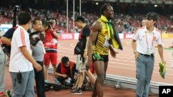 Jamaica's Usain Bolt walks away after being hit by a videographer on a Segway as Bolt celebrated winning the men's 200m final at the World Athletics Championships at the Bird's Nest stadium in Beijing, Aug. 27, 2015.