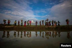 FILE - Rohingya refugees are reflected in rainwater along an embankment next to paddy fields after fleeing from Myanmar into Palang Khali, near Cox's Bazar, Bangladesh, Nov. 2, 2017.