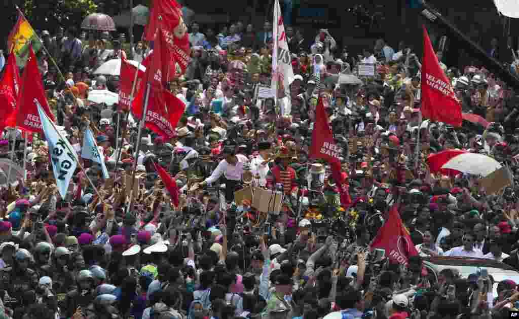 PresidenJoko Widodo menyalami warga di tengah kerumunan rakyat dalam parade jalanan menyusul pelantikannya di Jakarta (20/10). (AP/Mark Baker)