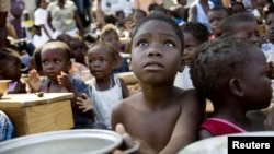 A child awaits for the distribution of meals by WFP in Haiti.