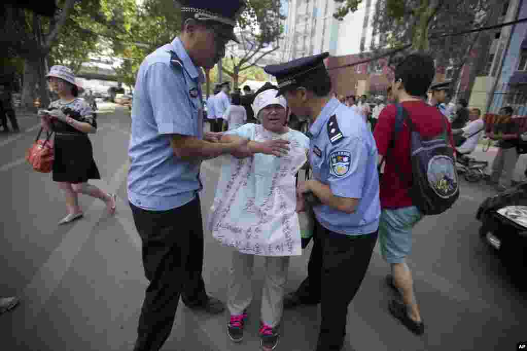 "Chinese police officers attempt to remove a woman protesting with the words ""unjust"" written on a banner outside the Jinan Intermediate People's Court in Jinan, eastern China's Shandong province, August 21, 2013."