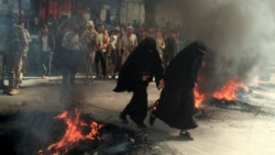 Women run past burning tires during protests against the deteriorating economic situation and the devaluation of the local currency, in Taiz, Yemen, Sept. 27, 2021.
