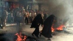چند زن در حال عبور از کنار لاستیکهای به آتش کشیده شده در میانه تظاهرات علیه وضعیت اقتصادی نابسامان و کاهش ارزش پول یمن؛ تعز، ۵ مهر ۱۴۰۰