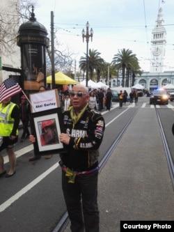 """北美崔哥告诉美国之音,旧金山集会游行时他举梁彼得案中死亡黑人青年格雷的像,他说:""""中国有句话,人死为大。"""""""