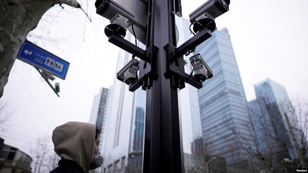 上海街头监控摄像机下的一名戴口罩的行人。(2020年3月4日)(photo:VOA)