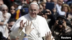Pope Francis waves as he leaves after the Palm Sunday mass at Saint Peter's Square, March 24, 2013.