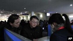 북한 평양 공항의 '고려링크' 부스에서 휴대전화를 대여하는 외국인들.