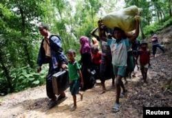 Orang Rohingya berjalan menuju tempat penampungan darurat dekat perbatasan Bangladesh-Myanmar, setelah dilarang oleh anggota Penjaga Perbatasan Bangladesh (BGB), untuk memasuki Bangladesh, di Cox's Bazar, Bangladesh, 28 Agustus 2017.