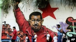 People pass in front a mural depicting Venezuela's President Hugo Chavez in Caracas, Venezuela, February 2, 2011