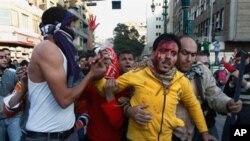 이집트 카이로에서 경찰의 진압으로 부상당한 시위자를 동료 시위자가 부축하고있다.