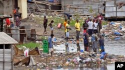 People stand on the polluted shoreline in West Point neighborhood, an area heavily effected by the Ebola virus, where residents are not being allowed to leave to prevent the spread of Ebola, in Monrovia, Liberia, Aug. 27, 2014.