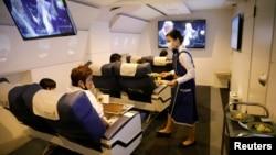 ایک جاپانی ایئرلائن کی ایئر ہوسٹس دوران پرواز مسافروں کو کھانا فراہم کر رہی ہے۔ (فائل فوٹو)