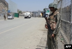 FILE - Pakistani soldiers patrol at the Torkham border crossing between Pakistan and Afghanistan in Pakistan's Khyber Pass on June 14, 2016. Both sides are blaming each other for a recent spike in tensions at the frontier.