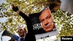 Protesters taking part in a rally in Tel Aviv hold signs calling upon Israeli Prime Minister Benjamin Netanyahu to step down, Feb. 16, 2018.