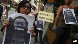 Pro-democracy protesters carry portraits of detained Chinese artist Ai Weiwei urging for his release before walking to a China's liaision office in Hong Kong April 10, 2011. China has extended a crackdown on dissidents, human rights lawyers and protesters