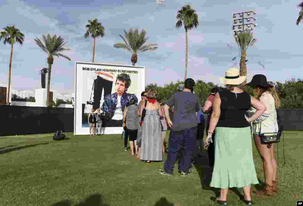 "Festival goers wait in line to be photographed against a billboard of Bob Dylan's album ""Highway 61 Revisited"" on day 1 of the 2016 Desert Trip music festival at Empire Polo Field, Oct. 7, 2016, in Indio, California."