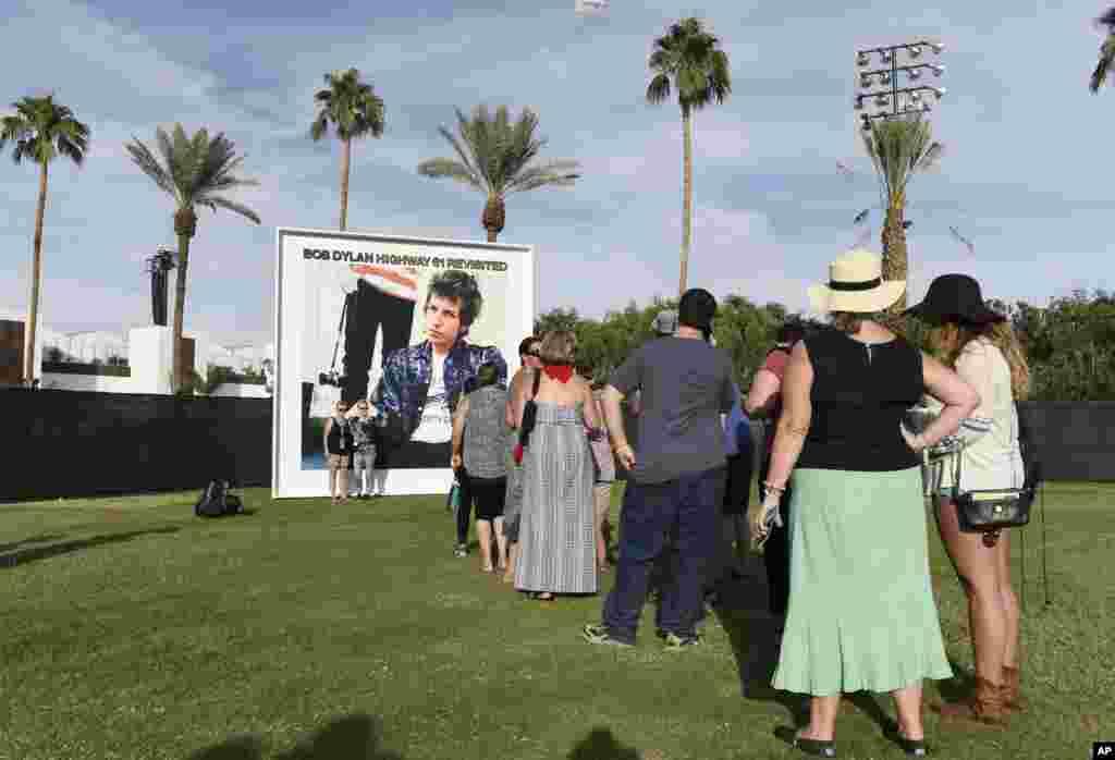 អ្នកចូលរួមក្នុងពិធីបុណ្យតម្រង់ជួរចាំចូលថតរូបជាមួយនឹងផ្ទាំងរូបថតអាល់ប៊ុម «Highway 61 Revisited» របស់លោក Bob Dylan នៅក្នុងថ្ងៃទីមួយ នៃពិធីបុណ្យតន្ត្រី Desert Trip នៅឯទីលាន Empire Polo កាលពីថ្ងៃទី៧ ខែតុលា ឆ្នាំ២០១៦ នៅក្នុងទីក្រុង Indo រដ្ឋ California។