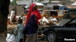 Perempuan dan dua anak menunggu kendaraan di pinggir jalan kota Maiduguri, negara bagian Borno, Nigeria, setelah militer mengumumkan jam malam (19/5). (Reuters/Afolabi Sotunde)