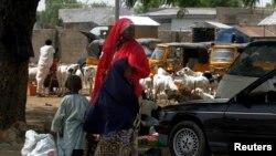 Wata mata da 'ya'yanta biyu a dab da tashar motar titin Jos a Maiduguri tana jiran shiga mota.