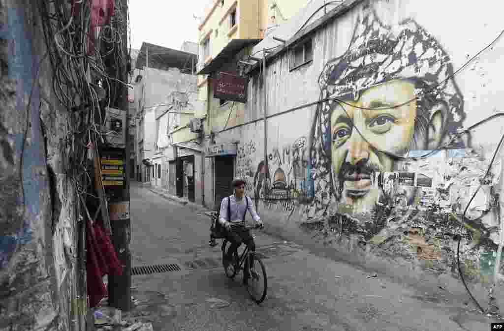Mohammed ជាងកាត់សក់ចល័តជនជាតិលីបង់ ដែលត្រូវបានស្គាល់ថា«Abo Tawila» ជិះកង់នៅតាមដងផ្លូវមួយជាយជំរំជនភៀសខ្លួនប៉ាឡេស្ទីន Burj al-Barajneh ភាគខាងត្បូងទីក្រុង Beirut ប្រទេសលីបង់។