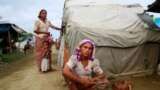 Sinnuyar Baekon sits in front of her hut at a refugee camp outside Sittwe, the capital city of the Rakhine state, Myanmar, June 9, 2014.