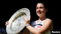 La française Marion Bartoli brandit le trophée Venus Rosewater Dish, après sa victoire sur l'Allemande Sabine Lisicki lors de leur dernier match de tennis en simple aux championnats de tennis de Wimbledon, Londres, 6 juillet 2013.