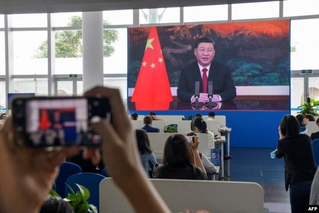 采访博鳌论坛的记者们在媒体厅观看屏幕上显示的中国国家主席习近平在开幕式上讲话的视频。(2021年4月20日)