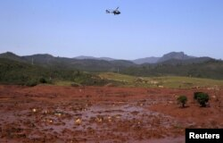 FILE - A helicopter flies over the Bento Rodrigues district, covered with mud after a dam owned by Vale SA and BHP Billiton Ltd burst in Mariana, Brazil, Nov. 6, 2015.