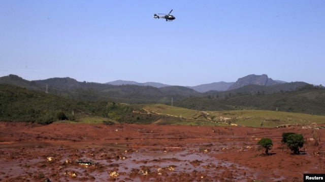 FILE - A helicopter flies over the Bento Rodrigues district, covered with mud after a dam owned by Vale SA and BHP Billiton Ltd. burst in Mariana, Brazil, Nov. 6, 2015.