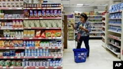 FILE - A woman shops at a supermarket in Cairo, Egypt.