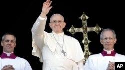 "Paus Fransiskus melambai kepada kepada massa usai memberikan pesan Natal ""Urbi et Orbi"" di depan basilika Santo Petrus, Vatikan hari Senin (25/12)."