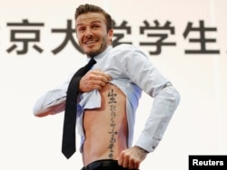 "Football star David Beckham displays a tattoo, as requested by students at Peking University, during a visit to Beijing, March 24, 2013. Its translation: ""Life and death are determined by fate, rank and riches decreed by Heaven."""