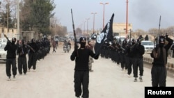 Combatientes del Estado Islámico en Irak y Levante desfilan en el pueblo sirio de Tel Abyad. También se han tomado dos ciudades iraquís.