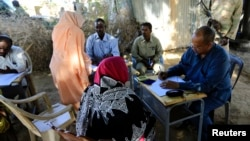 FILE - Yasir Ahmed Mohamed, seated at right, special prosecutor for crimes in Darfur, and his team talk to women during an investigation into allegations of mass rape in Thabit, Nov. 20, 2014.